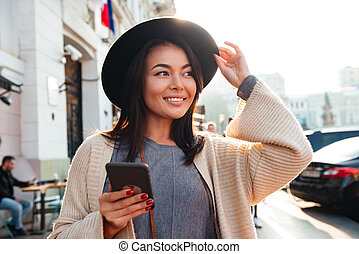 Portrait of a pretty smiling woman using mobile phone