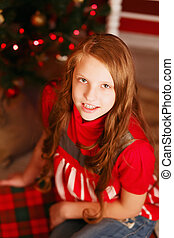 Portrait of a pretty teen girl with long hair in interior with Christmas decorations
