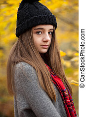 Portrait of a pretty teenage girl with autumnal colours in the background