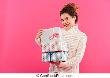 Portrait of a pretty woman holding stack of gift boxes