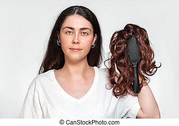 Portrait of a pretty woman holds a comb with a wig on it. White background. Concept of hair care and hair loss.