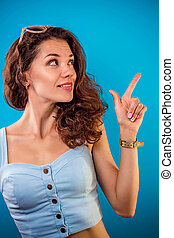 Portrait of a pretty woman pointing at something.