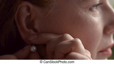 Portrait of a pretty woman putting on earring and looking at...