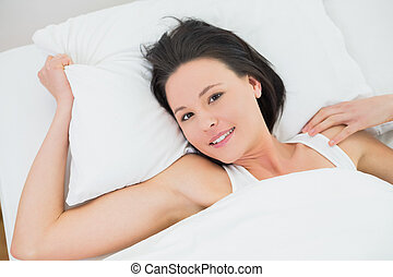 Portrait of a pretty woman resting in bed