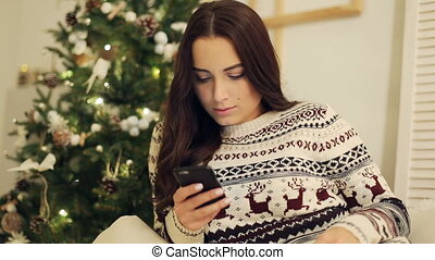 Portrait of a pretty woman using her mobile phone. High ISO image