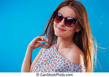 Portrait of a pretty woman wearing sunglasses. Summer outfit. Happy stylish girl