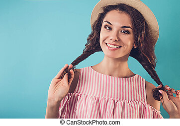 Portrait of a pretty woman with braids. Stylish summer outfit. Fashion