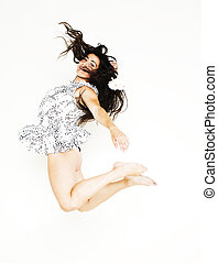 Portrait of a pretty young asian woman jumping in joy over white background, flying hair, lifestyle people concept