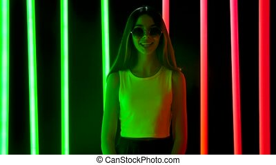 Portrait of a pretty young beautiful woman in stylish round sunglasses looking at the camera with a wow enthusiastic expression. Brunette with long hair posing against a smoky studio background with bright multicolored neon tubes. Slow motion.
