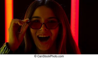 Portrait of a pretty young beautiful woman in stylish sunglasses looking at the camera with a wow enthusiastic expression. Brunette with long flowing hair posing against a smoky studio background with bright multicolored neon tubes. Close up. Slow motion.
