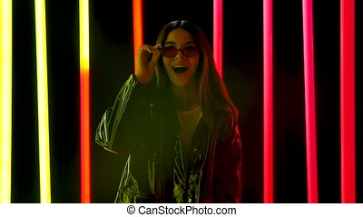 Portrait of a pretty young beautiful woman in stylish sunglasses looking at the camera with a wow enthusiastic expression. Brunette with long flowing hair posing against a smoky studio background with bright multicolored neon tubes. Slow motion.