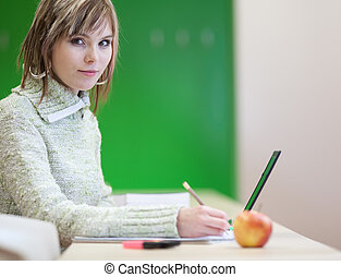 portrait of a pretty young blonde college student smiling while taking notes in a her college major class