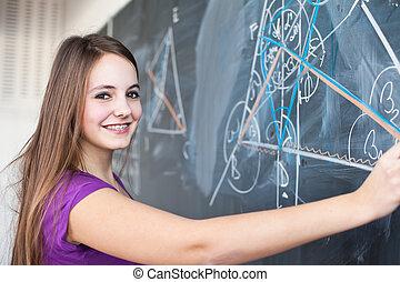 student writing on the blackboard