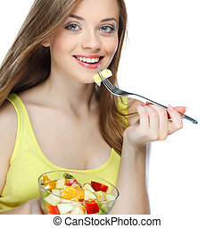 Portrait of a pretty young woman eating fruit salad isolated...