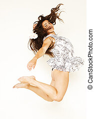 Portrait of a pretty young woman jumping in joy over white background