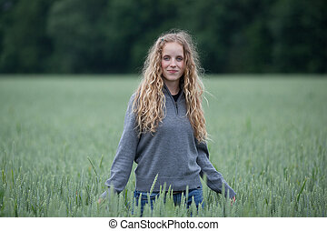 portrait of a pretty young woman standing in a green field - looking happy/content/relaxed