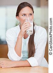 Portrait of a radiant woman drinking milk