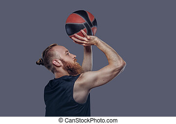 Portrait of a redhead basketball player in a black sportswear holding a ball with hands overhead, isolated on a dark textured background.