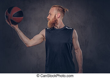 Portrait of a redhead basketball player in a black sportswear holding ball, isolated on dark textured background.