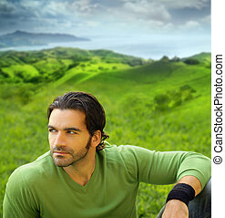 Portrait of a relaxed good-lookiing young man in beautiful natural setting wearing a green sweater
