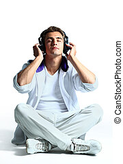 Portrait of a relaxed young man listening to music on headphone against white background