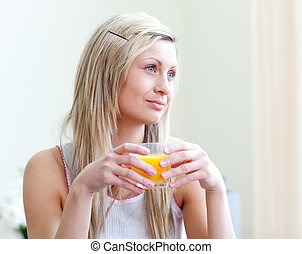 Portrait of a relaxed young woman drinking an orange juice