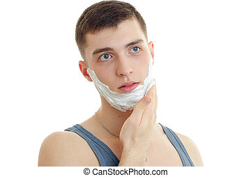 Portrait of a remarkable young man who looks away and shaving foam on beard close-up