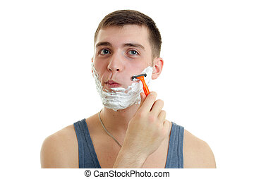 Portrait of a ridiculously young guy with foam on his face who shaves his beard machine
