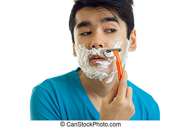 Portrait of a ridiculously young man in a t-shirt who looks away with foam on your face and shaves his beard machine