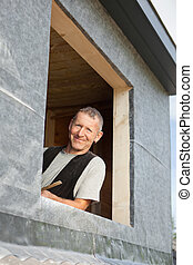 Portrait of a roofer looking by a dormer window