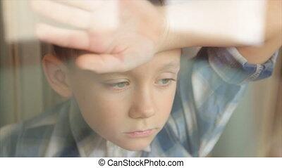Portrait of a sad boy near the window - A sad child looks...