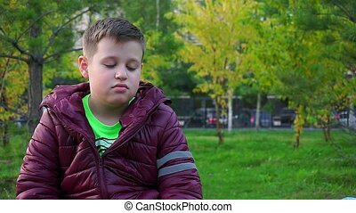 Portrait of a sad boy. Sitting in the Park, he's lost.