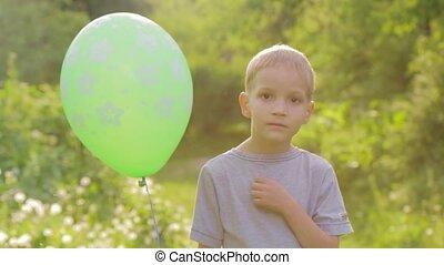 Portrait of a sad boy with a balloon