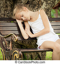 portrait of a sad child  sitting on a bench in the park under the tree