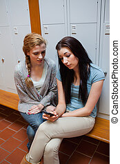 Portrait of a sad student showing a text message to her friend
