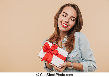 Portrait of a satisfied young girl holding present box