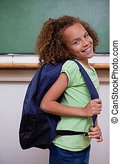 Portrait of a schoolgirl showing her backpack in a classroom