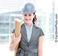 Portrait of a self-assured female architect holding blueprints