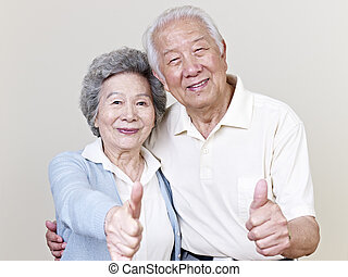 portrait of a senior asian couple, thumbs up.