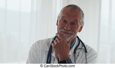 Portrait of a senior doctor with smartwatch in office. -...