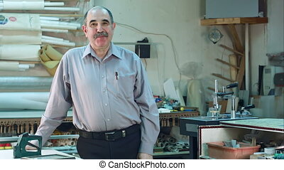 Portrait of a senior male business owner behind the counter of his frame workshop, standing and talking to a camera