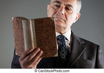 Portrait of a senior man reading from an old book