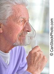 Portrait of a senior man with inhaler