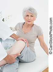 Portrait of a senior woman getting her leg examined