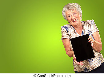 Portrait Of A Senior Woman Holding A Digital Tablet On Green...