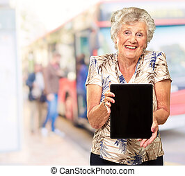 Portrait Of A Senior Woman Holding A Digital Tablet, Outdoor