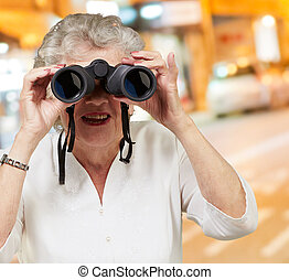 Portrait of a senior woman looking through binoculars
