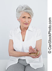 Portrait of a senior woman with hand in wrist brace sitting...