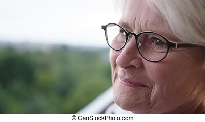 Portrait of a senior lady with smile but sad eyes standing the balcony . High quality 4k footage