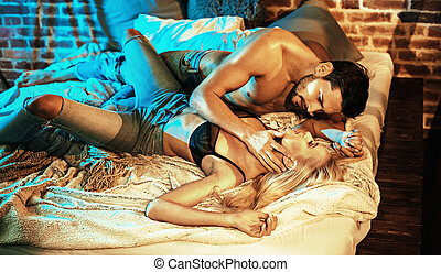 Portrait of a sensual couple relaxing in the bedroom